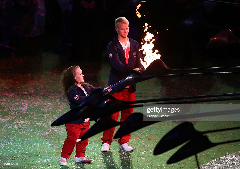 Swimmer Eleanor Simmonds and athlete Jonnie Peacock light torches from the flame of the Paralympic cauldron as it is extinguished during the closing ceremony on day 11 of the London 2012 Paralympic Games at Olympic Stadium on September 9, 2012 in London, England.