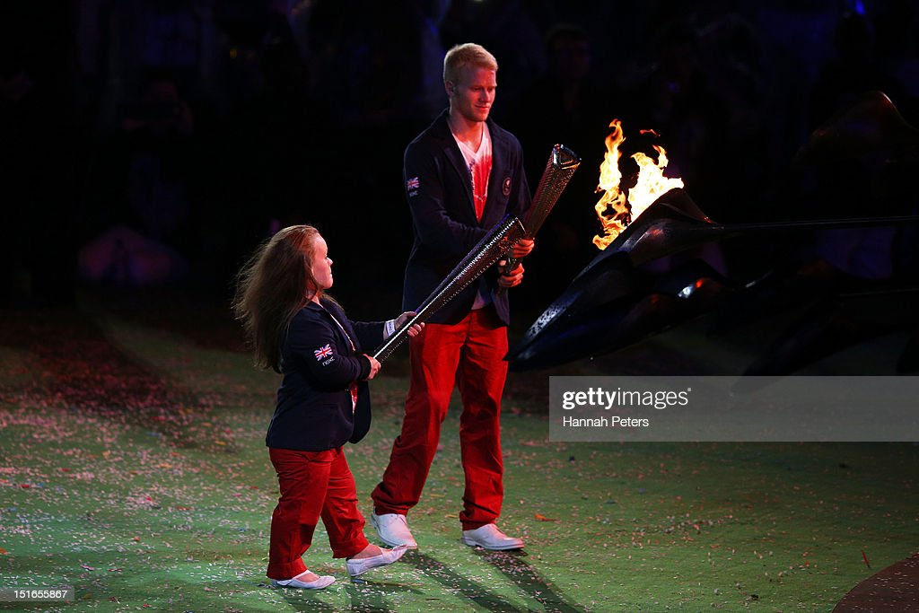 Swimmer Eleanor Simmonds and athlete Jonnie Peacock of Great Britain light torches from the flame of the Paralympic cauldron as it is extinguished during the closing ceremony on day 11 of the London 2012 Paralympic Games at Olympic Stadium on September 9, 2012 in London, England.