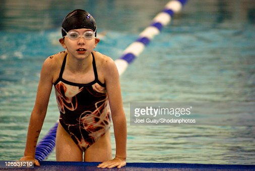 Swimmer girl pushup out of pool in goggles