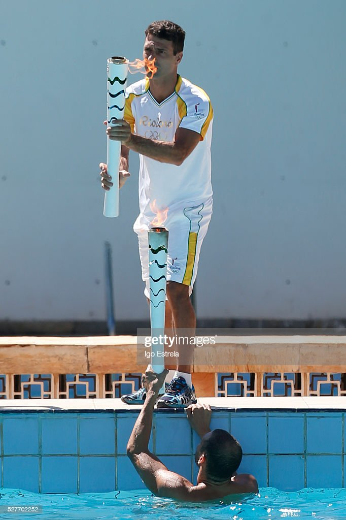Swimmer Icarus Pereira swim with the Olympic torch to pass to the Olympic athlete Diving <a gi-track='captionPersonalityLinkClicked' href=/galleries/search?phrase=Hugo+Parisi&family=editorial&specificpeople=4210586 ng-click='$event.stopPropagation()'>Hugo Parisi</a>, swimming in the pool water complex Claudio Coutinho. on May 3, 2016 in Brasilia, Brazil. The Olympic torch will pass through 329 cities from all states from the north to the south of Brazil, before arriving in Rio de Janeiro on August 5, for the lighting of the cauldron.
