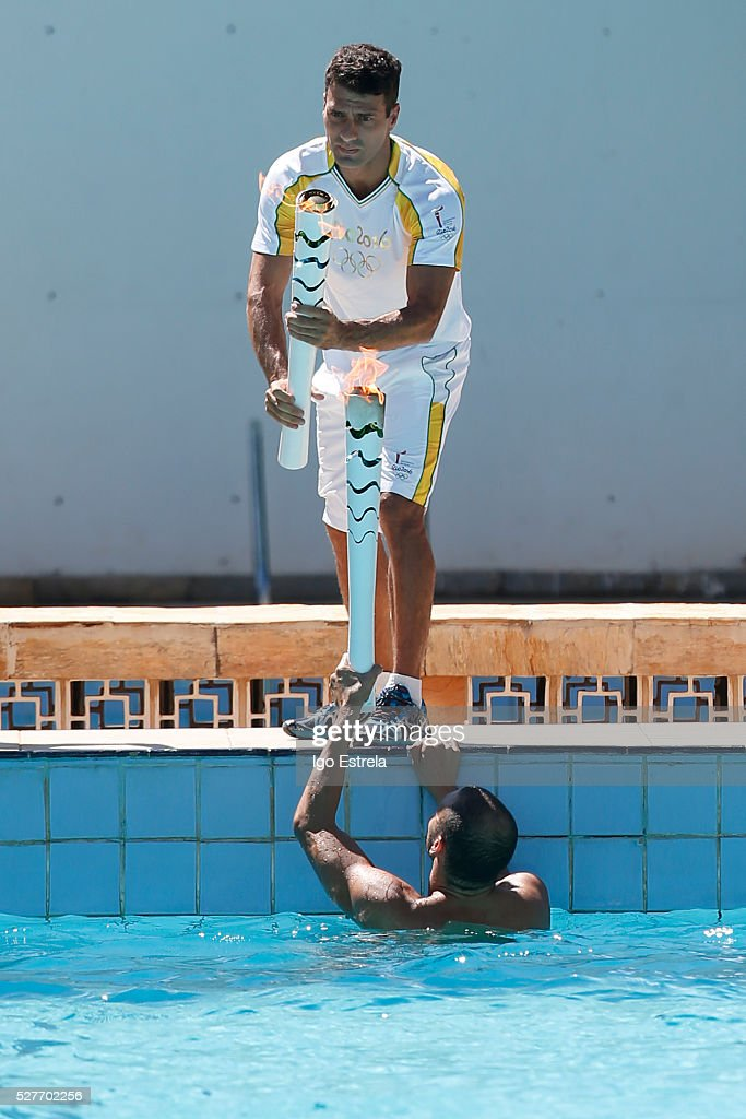 Swimmer Icarus Pereira swim with the Olympic torch to pass to the Olympic athlete Diving Hugo Parisi, swimming in the pool water complex Claudio Coutinho. on May 3, 2016 in Brasilia, Brazil. The Olympic torch will pass through 329 cities from all states from the north to the south of Brazil, before arriving in Rio de Janeiro on August 5, for the lighting of the cauldron.