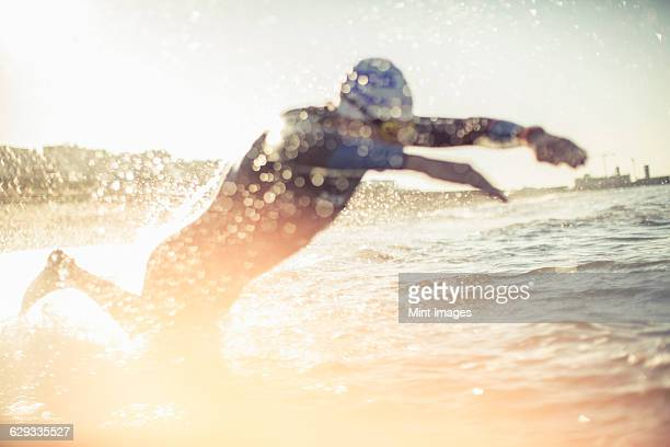 A swimmer in a wet suit running into the water, making a splash.