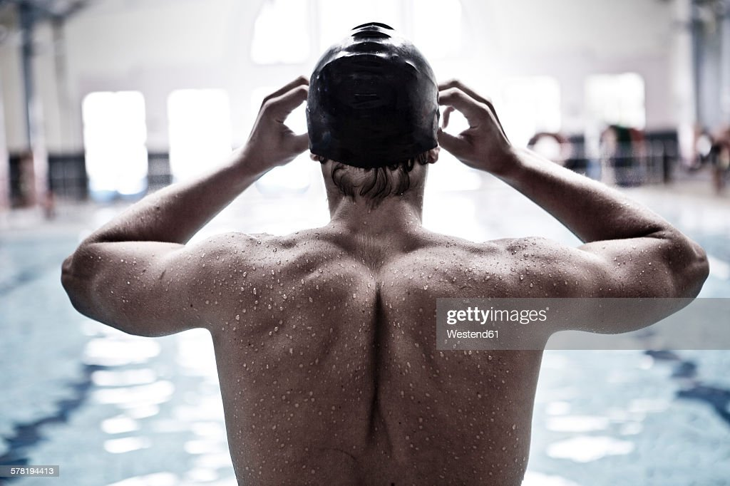 Swimmer in indoor pool putting on swimmming goggles