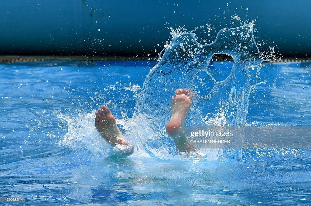 A swimmer jumps into the water of the public openair swimming pool in Neumuenster northern Germany on June 30 2015 Meteorologists forecast...