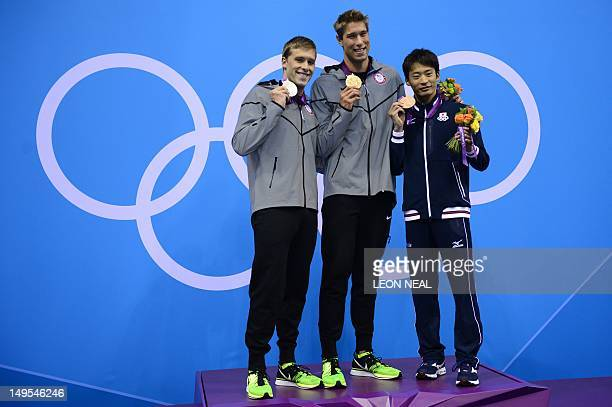 US swimmer Matthew Grevers poses on the podium with the gold medal flanked by silver medalist US swimmer Nick Thoman and bronze medalist Japan's Irie...