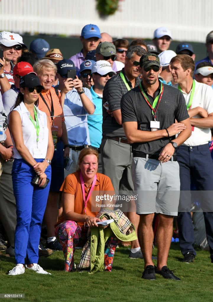 Swimmer Michael Phelps and his wife Nicole Johnson look on during the first round of the 2017 PGA Championship at Quail Hollow Club on August 10, 2017 in Charlotte, North Carolina.
