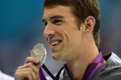 US swimmer Michael Phelps holds his gold medal on the podium of the men's 200m butterfly final during the swimming event at the London 2012 Olympic...