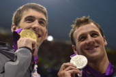 US swimmer Michael Phelps shows off his gold medal next to silver medalist US swimmer Ryan Lochte during a lap of honour after the podium ceremony...