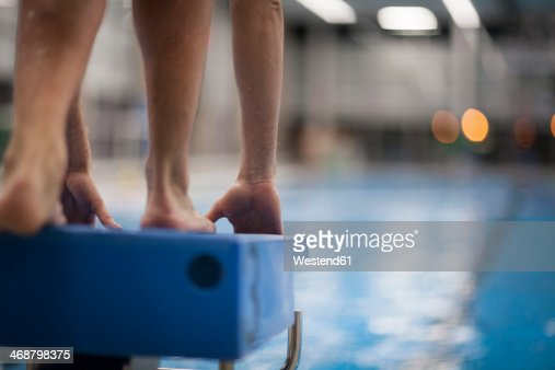 Swimmer On Starting Block At Indoor Swimming Pool Stock Photo