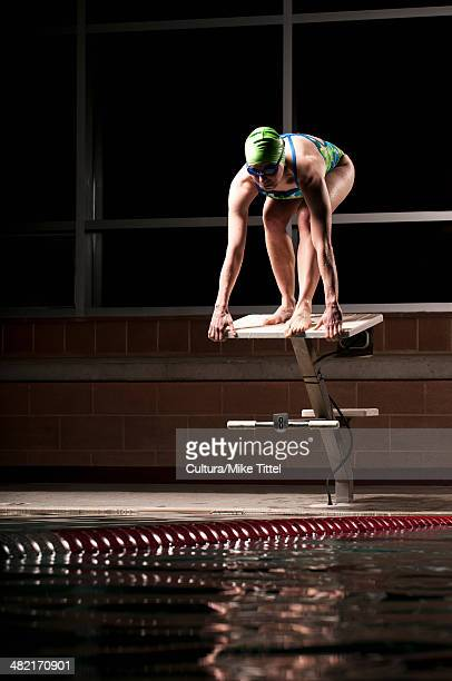Swimmer poised to dive into pool