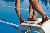 Swimmer preparing to dive from starting block, close-up feet