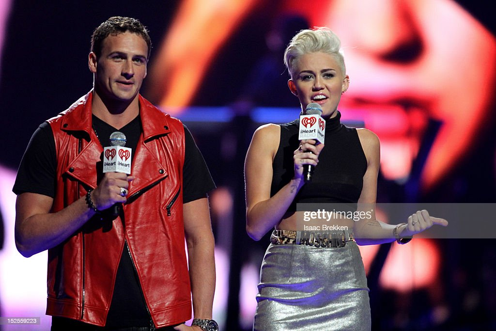 Swimmer Ryan Lochte (L) and singer Miley Cyrus speak onstage during the 2012 iHeartRadio Music Festival at the MGM Grand Garden Arena on September 21, 2012 in Las Vegas, Nevada.