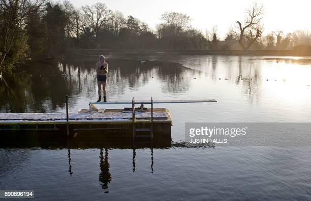 A swimmer stands on the diving board as he prepares to swim in the ice cold water at Highgate Men's Bathing Pond in north London on December 12 at...