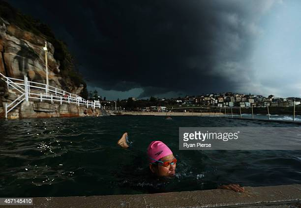 A swimmer swims laps in Bronte Ocean Pool as a severe storm hits Sydney at Bronte Beach on October 13 2014 in Sydney Australia