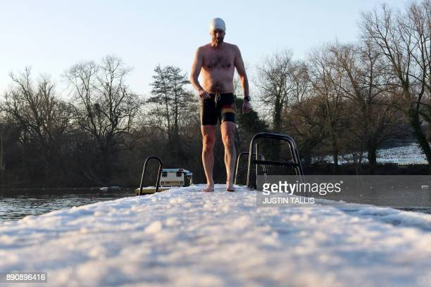 A swimmer walks along a snow covered jetty before swimming in the ice cold water at Highgate Men's Bathing Pond in north London on December 12 at...