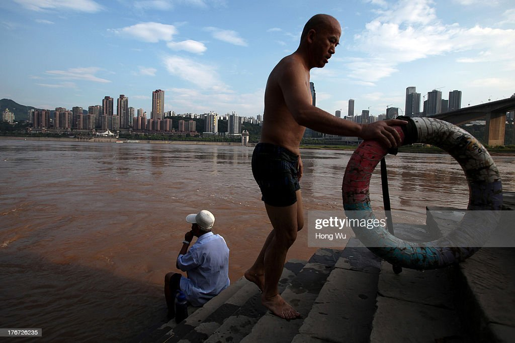 A Swimmer walks up the steps of the Yangtze River on August 4, 2013 in Chongqing, China. Chongqing is a major city in southwest China and became the municipality was created on 14 March 1997. It known as a 'Mountain City' and 'River City' was constructed on the mountain and along the Yangtze River.