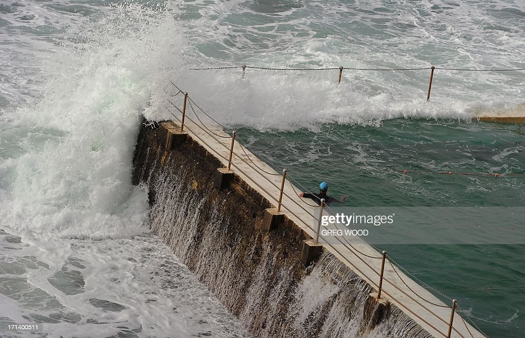 A swimmer (C) watches as a large wave flows over the wall of the Bondi Baths at Bondi Beach near Sydney on June 24, 2013. Expected extreme weather did not arrive in Sydney but a large trough sitting off the coast has generated large damaging surf and king tides. AFP PHOTO / Greg WOOD