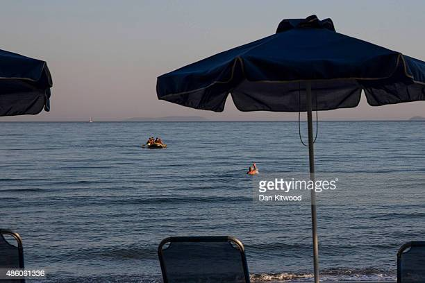 A swimmer waves as migrants paddle towards the shore after completing a journey in a small dinghy crossing a three mile stretch of the Aegean Sea...