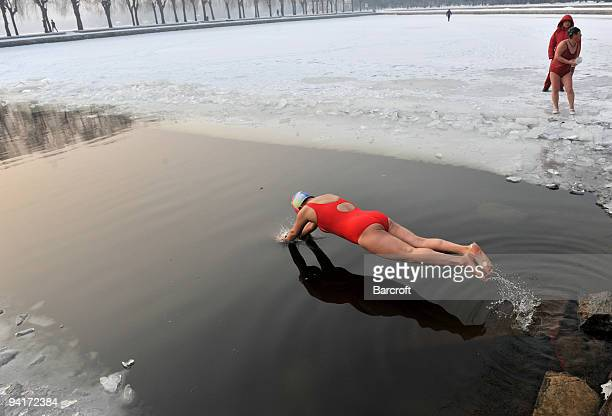 Swimmers brave the icey waters by taking a dip in a frozen lake Wednesday December 9 2009 in Shenyang in China's Liaoning province The temperature...
