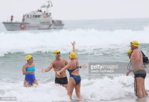 Swimmers celebrate after coming into the beach after a 10 kilometer swim which took them across the United StatesMexico border on Friday May 5 2017...