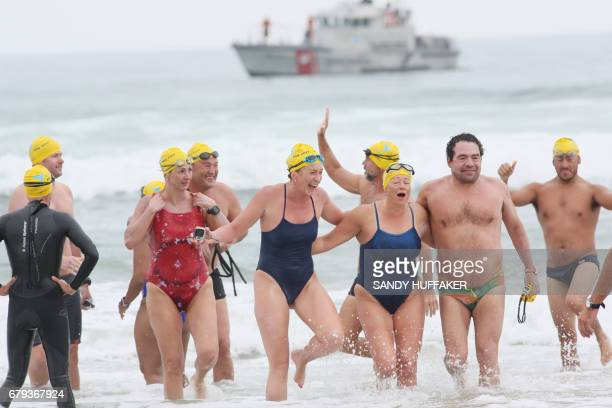 Swimmers celebrate after coming into the beach after a 10 Kilometers swim which took them across the United StatesMexico border on Friday May 5 2017...