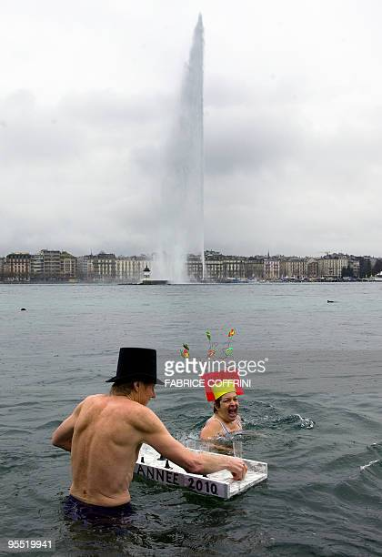 Swimmers celebrate with champagne in the 6 degree water of Lake Geneva as the fountain spouts in the background during the New Year's swim on January...