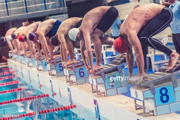 swimmers crouching on starting block ready to jump