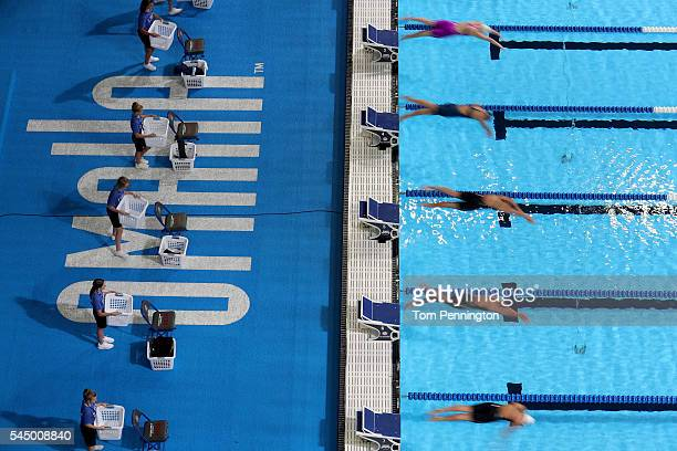 Swimmers dive in to compete in the second heat of the Women's 50 Meter Freestyle during Day Seven of the 2016 US Olympic Team Swimming Trials at...