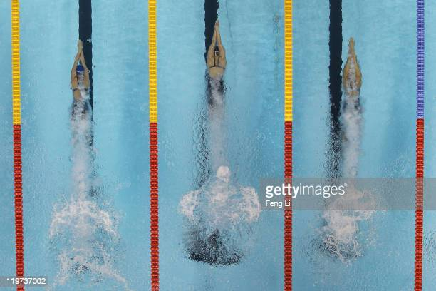 Swimmers dive into the water at the start of the first preliminary heat of the Women's 100m Butterfly during Day Nine of the 14th FINA World...