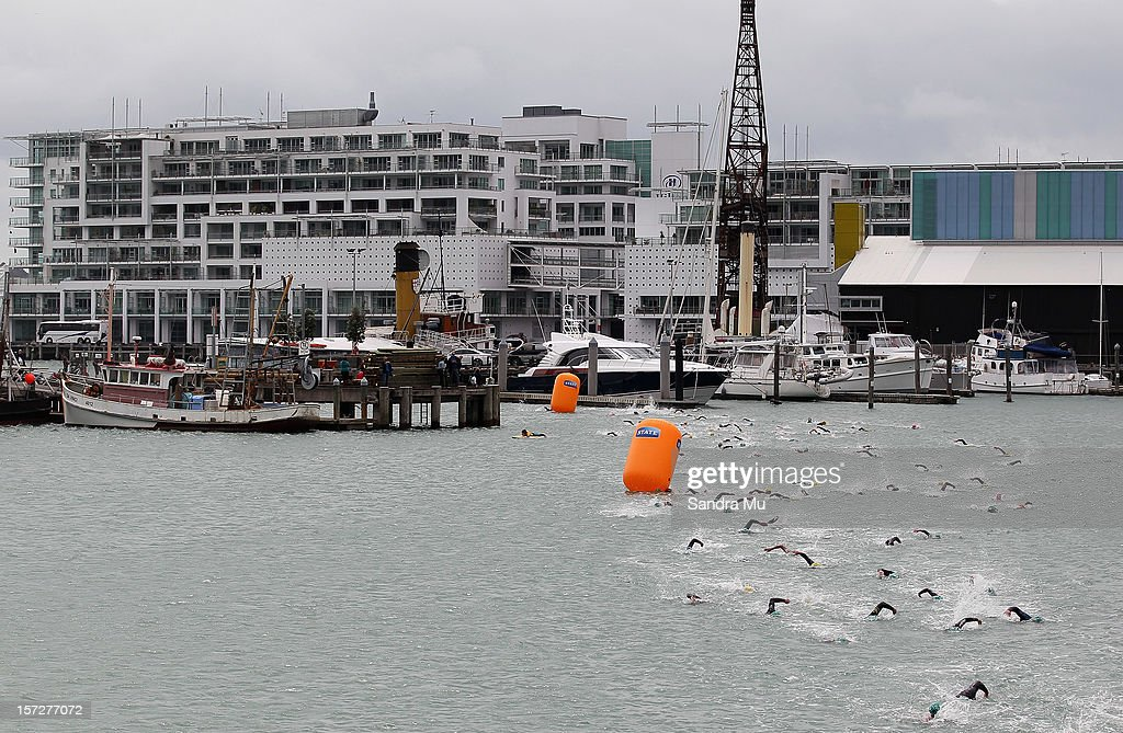 Swimmers enter into the Viaduct Harbour during the Auckland Harbour Crossing ocean swim event at the Viaduct Harbour on December 2, 2012 in Auckland, New Zealand.