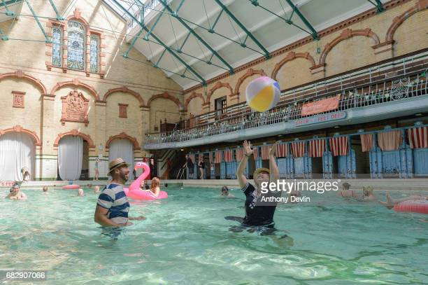 Swimmers in Victorian costume play with a beach ball as swimers enjoy the Men's First Class pool at Victoria Baths which are open today for the first...