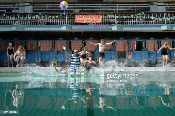 Swimmers jump into the Men's First Class pool at Victoria Baths which are open today for the first time in 20 years for a one off public swimming...