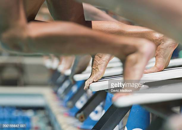 Swimmers jumping from starting blocks at start of race, low section