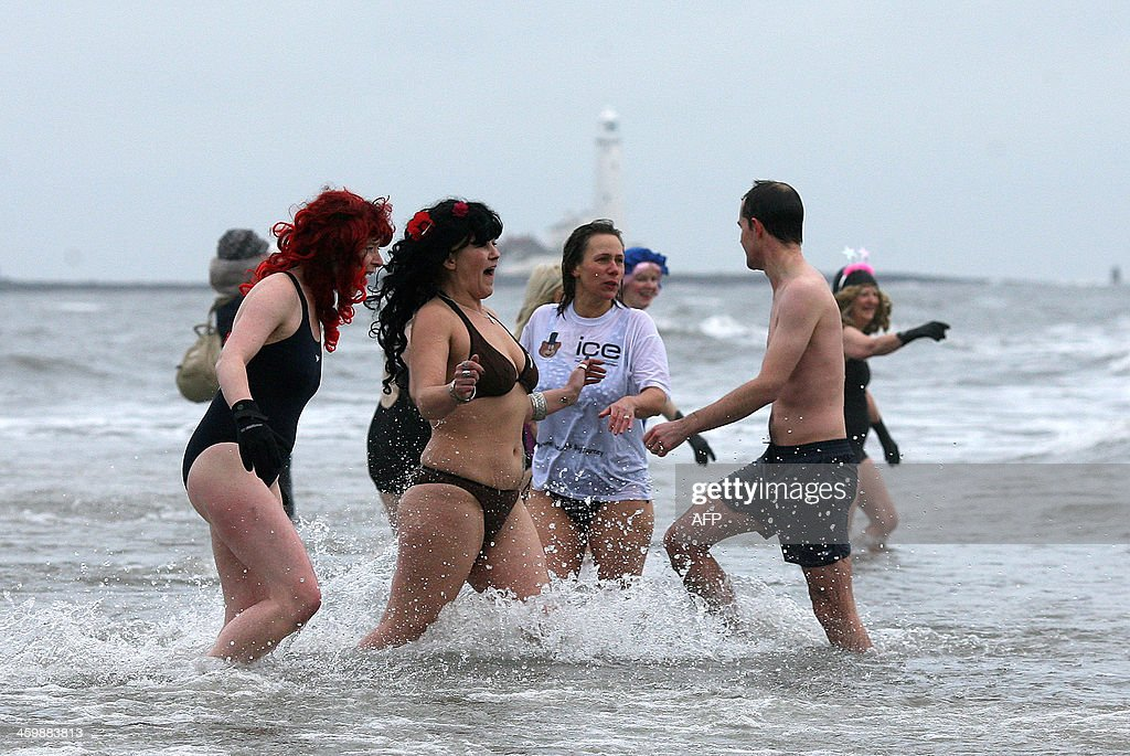 Swimmers, many in fancy dress brave the cold in the North Sea at the annual New Year's Day sea swim in Whitley Bay, northeast England on January 1, 2014. AFP PHOTO/ LINDSEY PARNABY.