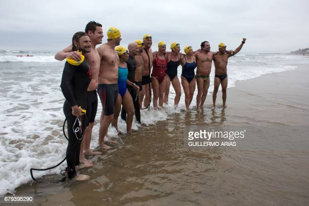 Swimmers participating in the PanAmerican Colibri Crossing pose for pictures upon arrival to the beach in Playas de Tijuana Mexico on May 5 after...