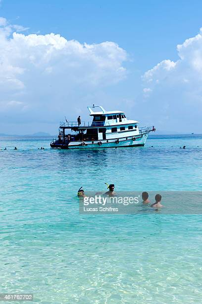 Swimmers snorkel near a paradise island part of Ko Phi Phi islands on December 16 2010 in the Adaman Sea Krabi province Thailand