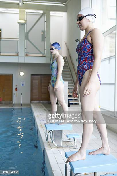 Swimmers standing on blocks in pool