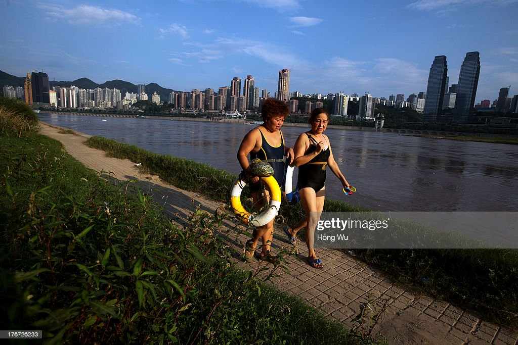 Swimmers walk along the Yangtze River on August 4, 2013 in Chongqing, China. Chongqing is a major city in southwest China and became the municipality was created on 14 March 1997. It known as a 'Mountain City' and 'River City' was constructed on the mountain and along the Yangtze River.