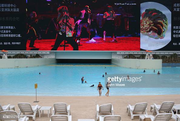 Swimmers walk on the beach inside the New Century Global Center on June 30 2015 in Chengdu China The Global Center opened in 2013 as the world's...