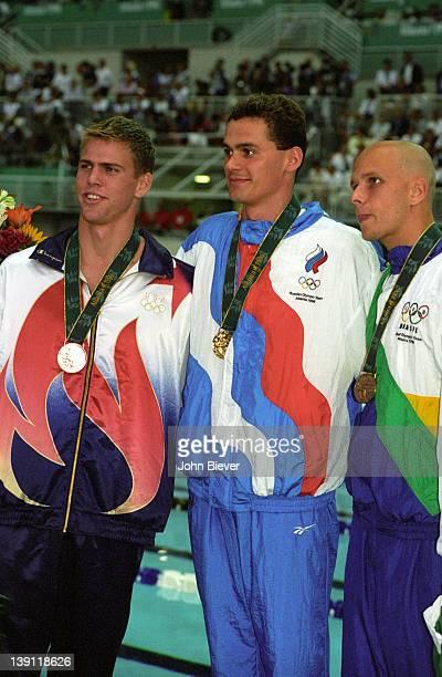 1996 Summer Olympics USA Gary Hall Jr Russia Alexander Popov and Brazil Fernando Scherer wearing medals after 50M Men's Freestyle Final at Georgia...