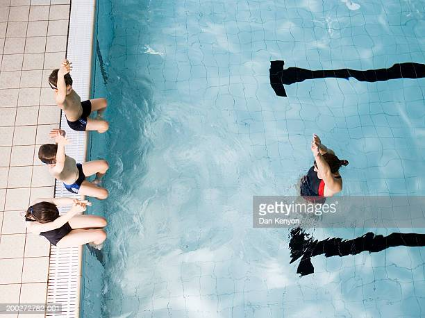 Swimming coach teaching children (8-10) on poolside to dive