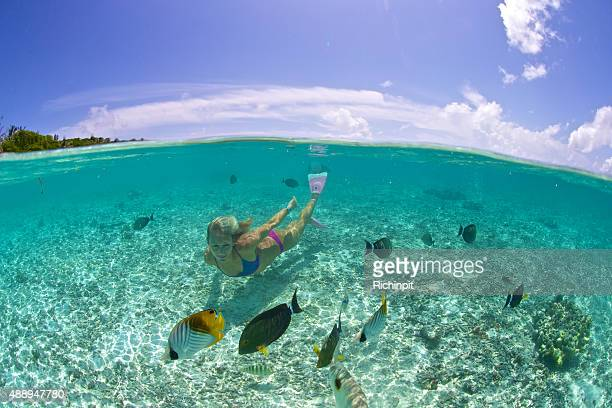 Swimming girl in tropical lagoon with fish and sky