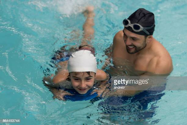 Swimming instructor teaching a boy in the pool