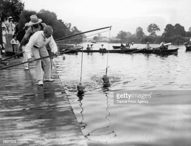 Two children suspended in the water by rope and poles are given a swimming lesson in the River Thames at Wallingford