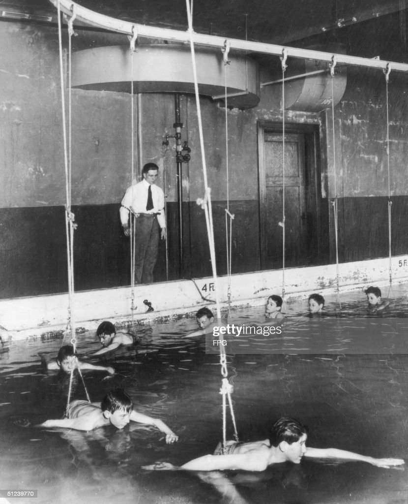 Circa 1930, Boys learn to swim on a kind of underwater merry-go-round at a school in Cincinnati.