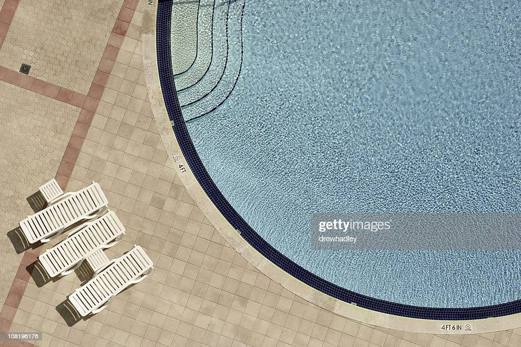 Swimming pool and lounge chairs : Stock Photo