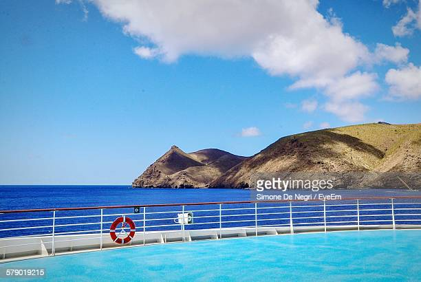 Swimming Pool In Cruise Ship In Front Of Island Against Sky