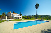 stone house finca with big swimming pool in well-kept garden on sunny day with clear blue sky
