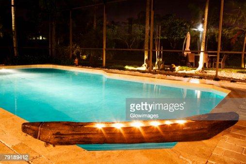 Swimming pool lit up at night : Stock Photo