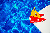 Swimming pool detail with toy boat on diving board.